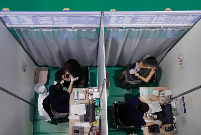 올해 마지막 단계인 코로나19 4분기 백신 접종 세부계획이 오후 발표된다. 전국민의 74%가 한차례 이상 백신을 접종한 만큼 남은 4분기에는 소아·청소년과 임산부 대상 접종이 시작되고 고위험군을 대상으로 한 부스터샷에 초점이 맞춰질 전망이다. 사진은 서울 서대문구 북아현문화체육센터에 마련된 코로나19 백신접종센터를 찾은 시민들이 백신 접종을 하고 있는 모습. 연합뉴스