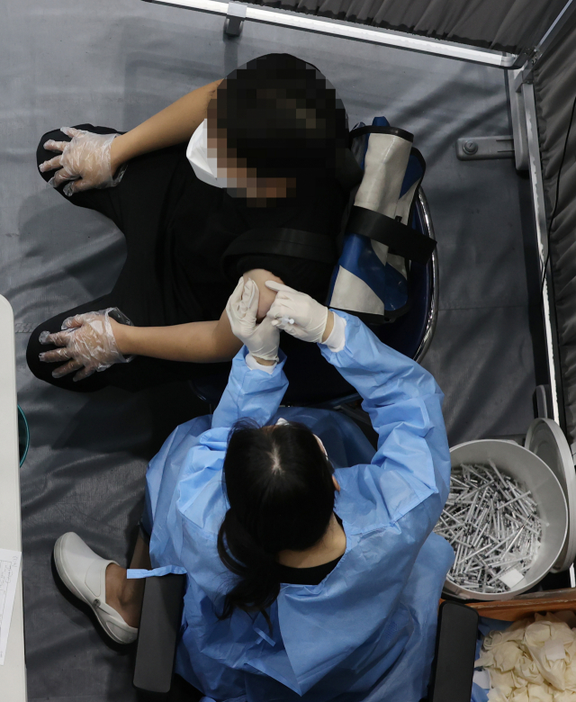 13일 오후 서울 송파구 체육문화회관에 설치된 송파구 백신접종센터에서 한 시민이 코로나19 백신 접종을 받고 있다. 정부가 내달 초 '단계적 일상회복'으로의 방역 체계 전환을 예고한 가운데, 국내 신종 코로나바이러스 감염증 백신 접종 속도가 빨라지면서 기존 일정이 앞당겨질 수 있다는 전망이 나왔다. 이날 정부 관계자에 따르면 방역 체계 전환의 기준이 되는 '전 국민 접종완료율 70%' 목표 달성 시점이 정부가 예상한 이달 23일보다 더 빨라질 가능성이 있는 것으로 나타났다. 연합뉴스