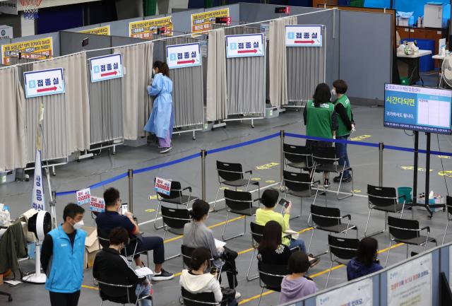 14일 송파구 체육문화센터에 마련된 코로나19 예방접종센터에 시민들이 백신 접종 후 이상반응 모니터링을 하고 있다. 연합뉴스