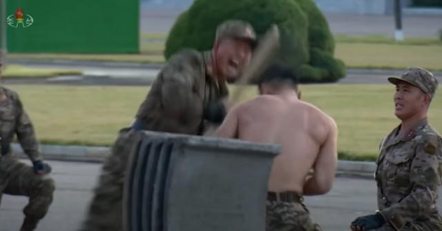 북한이 11일 개최한 국방발전전람회 '자위-2021' 개막식 행사에서 한 병사가 나무각목으로 상의를 탈의한 병사의 머리를 전력으로 가격하고 있다. 가디언 방송 캡쳐
